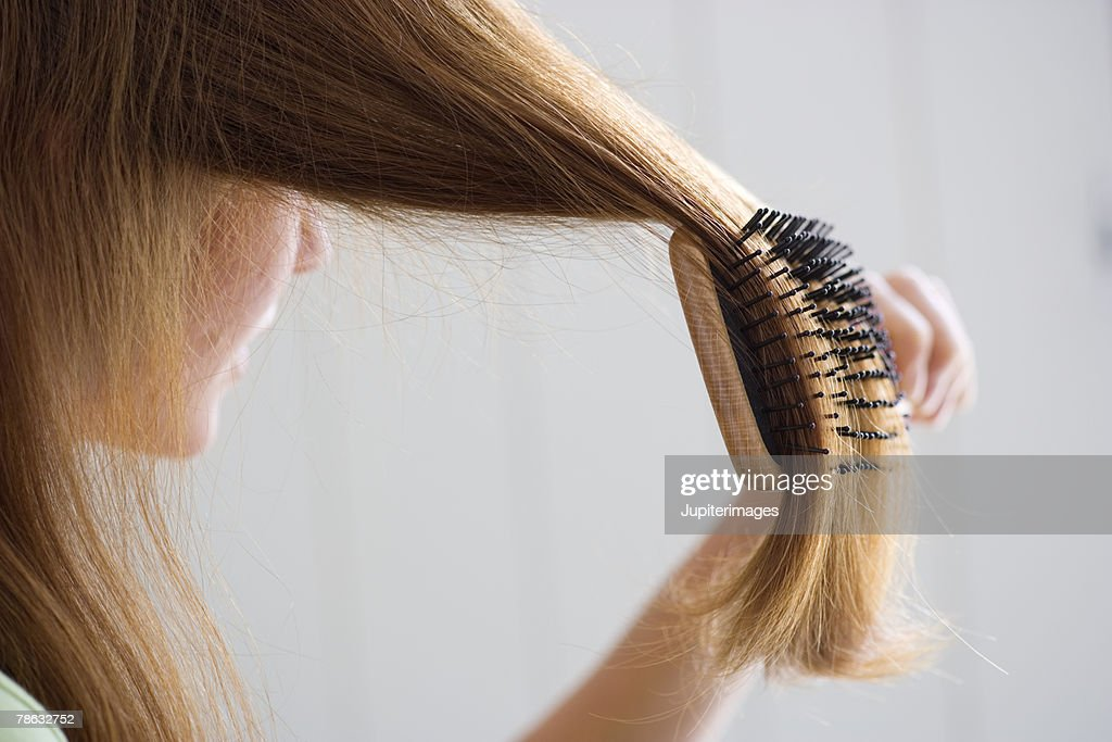 Person combing her hair : Stock Photo