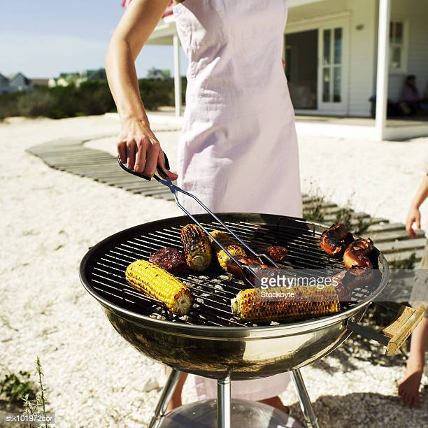 person cooking on an outdoor barbeque grill