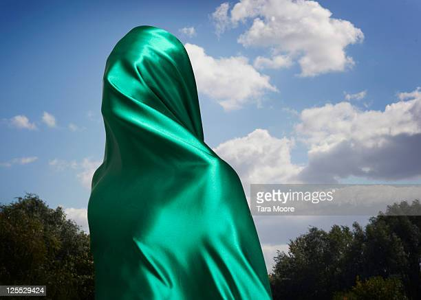 person covered by green material in country