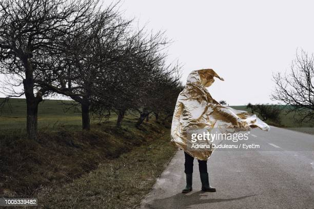 Person Covered With Gold Colored Textile On Road