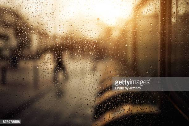 Person covering umbrella, by subway turnstiles in warm raining season viewed through window with droplets