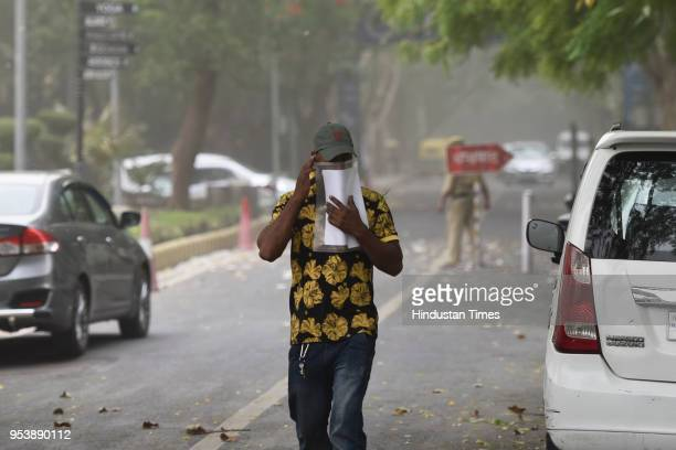 A person covers his face due to sudden dust storm on May 2 2018 in New Delhi India A squall and dust storm followed by heavy rain lashed the national...