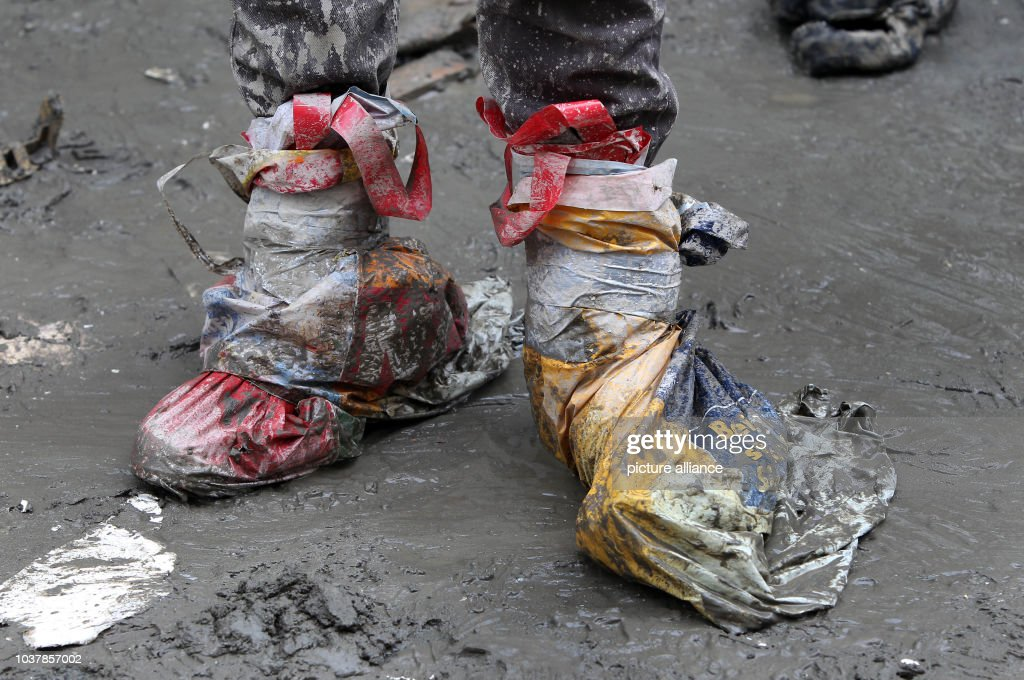 A Person Covers Their Shoes With Plastic Bags To Protect