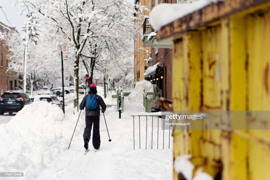 Person cross-country skiing on sidewalk in Montreal afetr a snowstorm. : Stock Photo