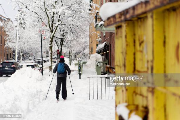 "person cross-country skiing on sidewalk in montreal afetr a snowstorm. - ""martine doucet"" or martinedoucet stock pictures, royalty-free photos & images"