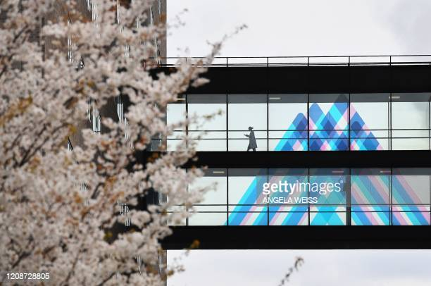 Person crosses a bridge in front of the Mount Sinai logo at Mt. Sinai Hospital on March 31, 2020 in New York. - The number of deaths in the United...