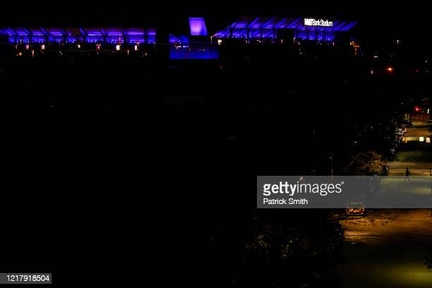 A person crosses an empty street as MT Bank Stadium home of the Baltimore Ravens NFL team is illuminated on April 09 2020 in Baltimore Maryland...