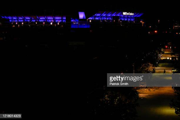 Person crosses an empty street as M&T Bank Stadium, home of the Baltimore Ravens NFL team, is illuminated on April 09, 2020 in Baltimore, Maryland....