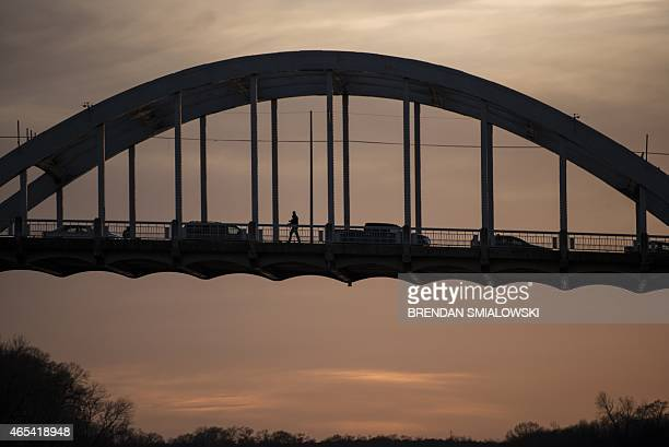 A person crosses the Edmund Pettus Bridge on March 6 2015 in Selma Alabama The march from Selma to Montgomery which US President Barack Obama will...