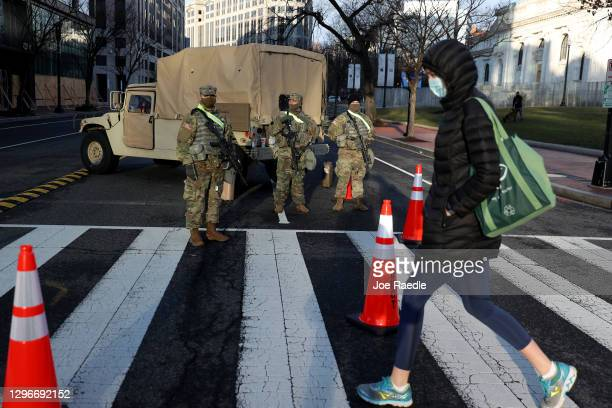 Person crosses the street at a road block guarded by Pennsylvania 112th Infantry Regiment National Guard on January 16, 2021 in Washington, DC. After...