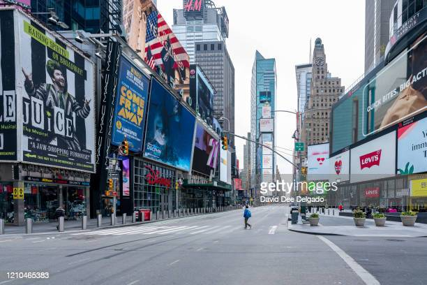 A person crosses the street at very quiet Times Square on April 20 in New York City During his daily coronavirus briefing New York Governor Andrew...
