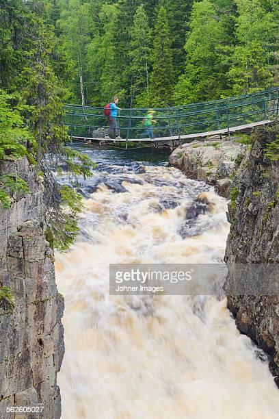 Person crossing footbridge over river