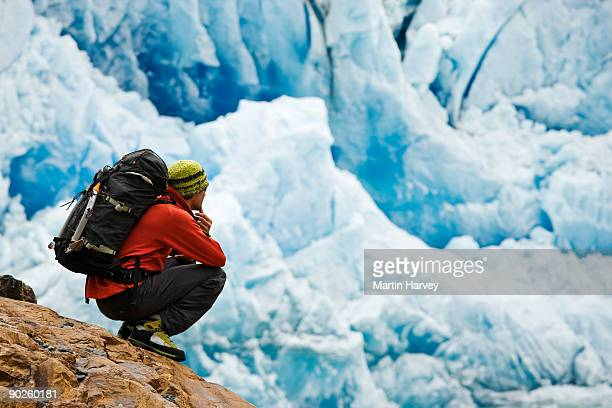 Person crouching on frozen mountainside