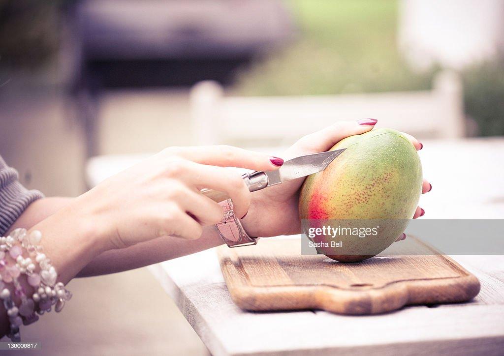 Person cutting Mango : Stock Photo