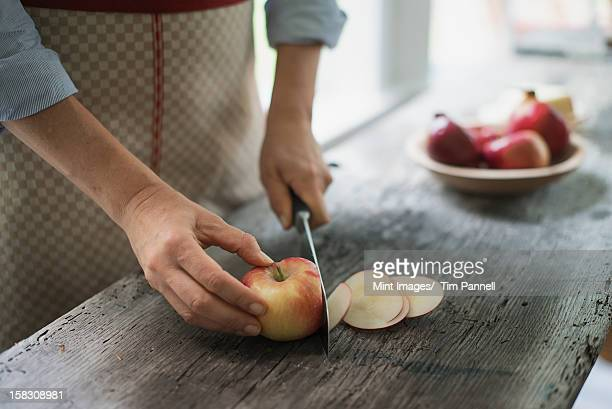 A person cutting up an organic apple.