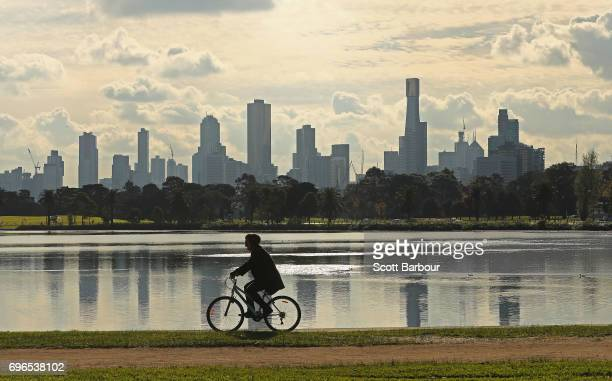 A person cycles along Albert Park Lake on an Autumn day with highrise and apartment buildings in the city in the background on June 16 2017 in...