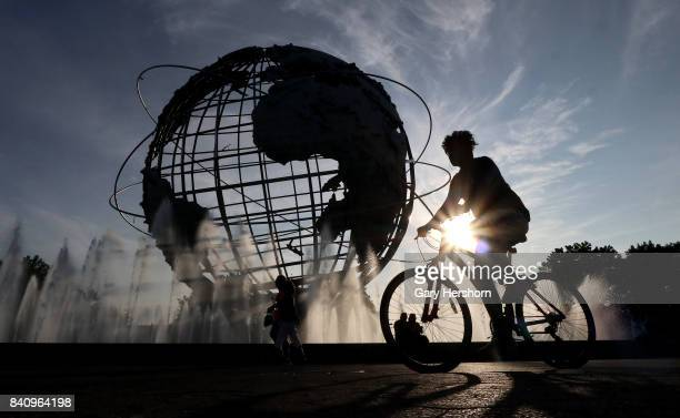Person cycles past the Unisphere, a spherical stainless steel representation of the Earth built for the 1964 World's Fair in Flushing Meadows Corona...