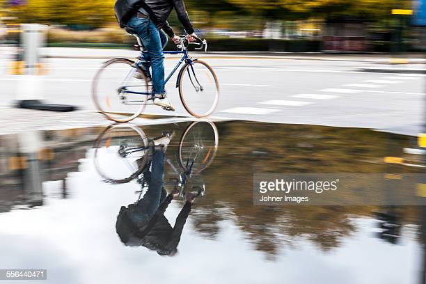 Person cycling along puddle