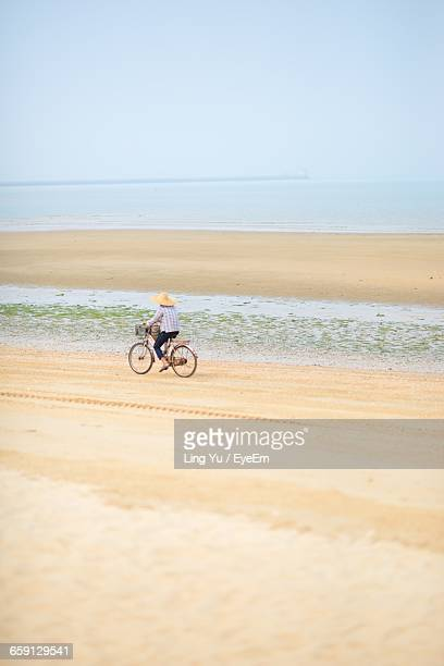 person cycling on beach against sky - zhanjiang stock photos and pictures