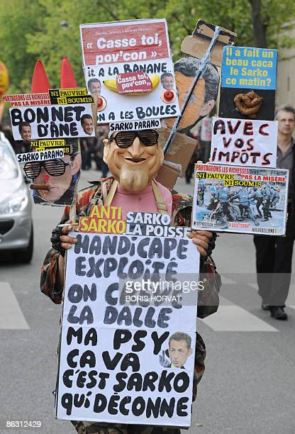 A person demonstrates holding signs making fun of French president Nicolas Sarkozy during the traditional May Day demonstration on May 1 2009 in...