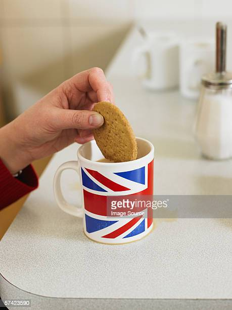 Person dipping biscuit in tea