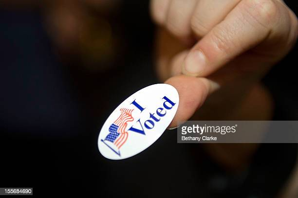 A person displayes an I Voted' sticker on November 6 2012 in London England US President Barack Obama and Republican presidential candidate Mitt...