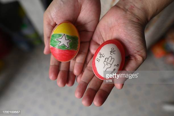 Person displays eggs, decorated with messages in support of protesters demonstrating against the military coup, in Yangon's Mingalar Taungnyunt...