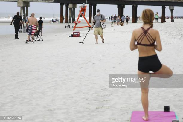 A person does yoga as others walk the beach in Jacksonville Beach Florida US on Saturday April 18 2020 Florida reported a total of 25269 confirmed...