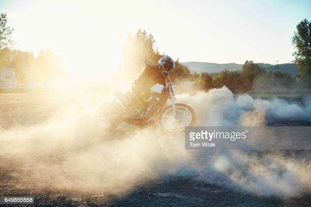 Person doing donuts on his motorbike in a rural setting