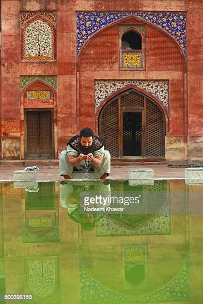 Person doing Wazoo to say pray in the Wazir Khan Mosque Lahore. The Wazir Khan Mosque in Lahore, Pakistan, is famous for its extensive faience tile...