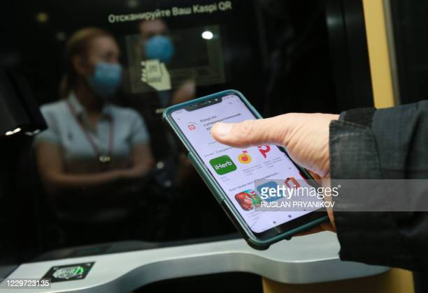 Person downloads the Kaspi application, Kazakhstan's payment systems and e-commerce leader, on their smartphone in Almaty, on November 5, 2020. -...