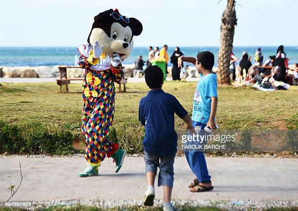 A person dressed as a cartoon character waves to Algerian children on the Sablettes seafront promenade on May 31 2014 in the capital Algiers Algerian...