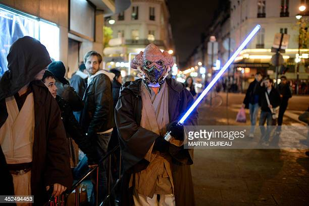 A person dressed as a jedi stands near fans waiting in line to see a Star Wars marathon at the Grand Rex theatre in central Paris on November 29 2013...