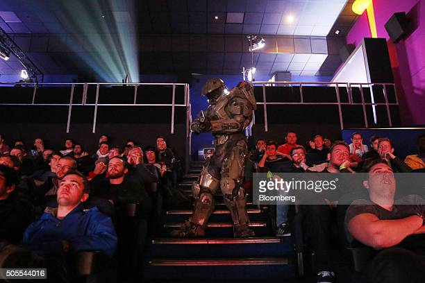 A person dressed as a Master Chief a character from the Halo video game franchise walks through the auditorium as fans watch professional videogame...