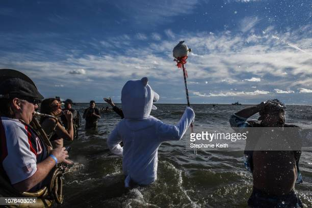 A person dressed as a polar bear leads the first procession into the Atlantic Ocean during the annual Polar Bear Plunge on New Year's Day in Coney...