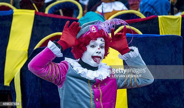 A person dressed as a whitefaced ''Clown Pete'' gestures during celebrations to mark the arrival of Sinterklaas the Dutch version of Santa Claus and...
