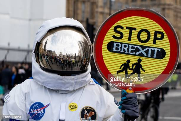 A person dressed as an astronaught holding a school traffic crossing sign reading Stop Brexit joins a march and rally organised by the proEuropean...
