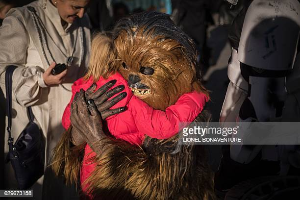 A person dressed as Chewbacca of Star Wars hugs a child on December 14 2016 at the Grand Rex cinema in Paris on the first day of the European release...