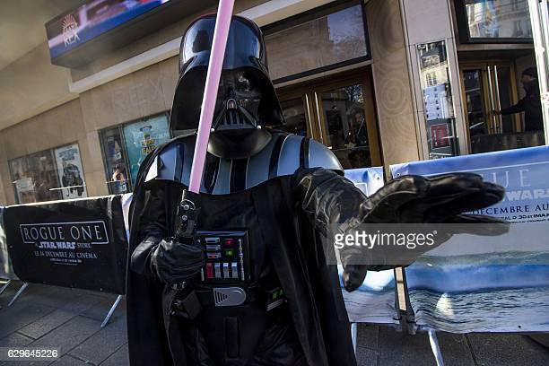 A person dressed as Dark Vador of Star Wars poses on December 14 2016 in front of the Grand Rex cinema in Paris on the first day of the European...