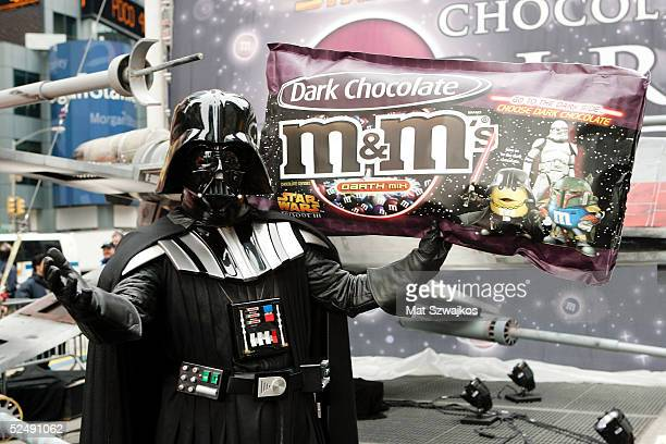 A person dressed as Darth Vader holds up a bag of candy at the unveiling of the new MM Star Wars candy in Times Square March 29 2005 in New York City