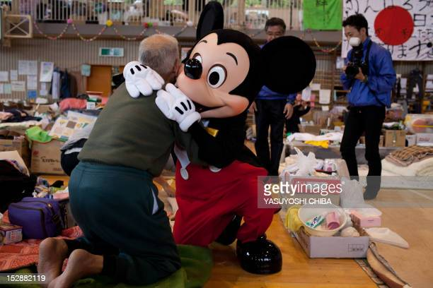 Person dressed as Disney character Mickey Mouse from the Tokyo Disney Resort hugs a man at an evacuation centre for people effected by the March 11...