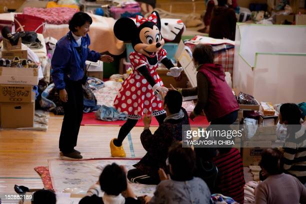 A person dressed as Disney character Minnie Mouse from the Tokyo Disney Resort greets evacuees at a centre for people effected by the March 11...