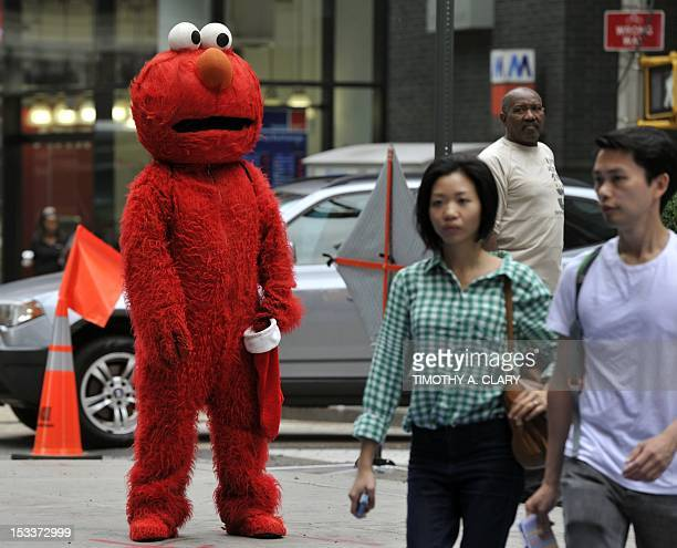 A person dressed as Elmo from the television show Sesame Street waits to pose for pictures with tourists in Times Square October 4 2012 GOP...