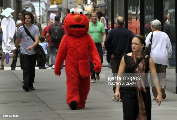 A person dressed as Elmo from the television show Sesame Street walks to pose for pictures with tourists in Times Square October 4 2012 GOP...