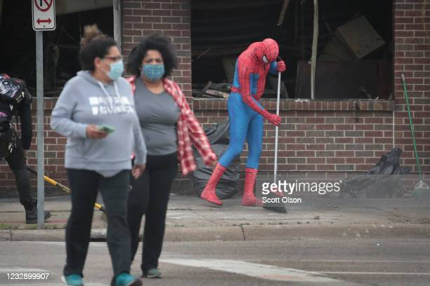 A person dressed as Spiderman sweeps the sidewalk as residents help to clean up following a night of rioting sparked by the death of George Floyd...