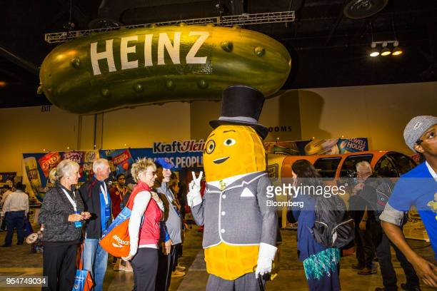 A person dressed as the Kraft Heinz Co Mr Peanut mascot gestures to attendees during a shareholders shopping day ahead of the Berkshire Hathaway...