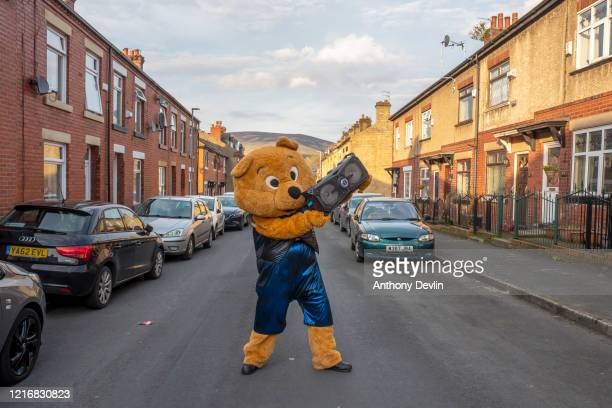 A person dressed in a bear costume plays music and dances in the streets to entertain people self isolating in Stalybridge on April 04 2020 in...