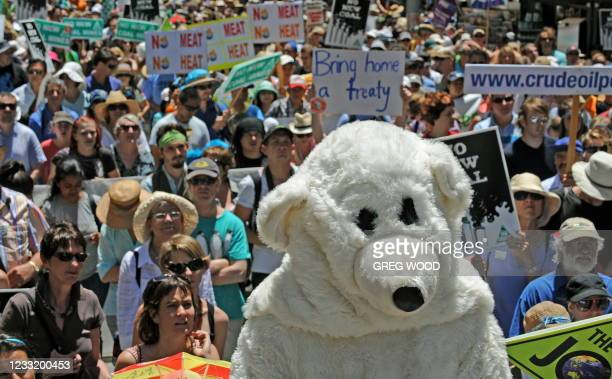 Person dressed in a polar bear suit joins a large crowd listening to speeches prior to marching through Sydney on December 12, 2009 as part of a...