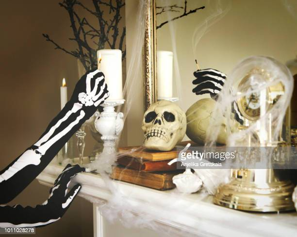person dressed in a skeleton costume lights a candles. halloween composition on fireplace - menschliches skelett stock-fotos und bilder