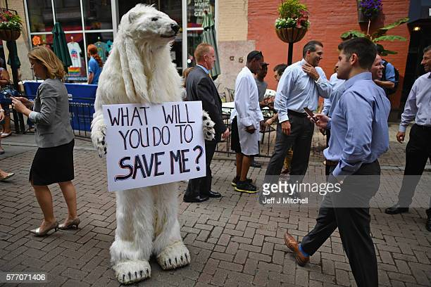 A person dressed in polar bear costume holds a sign as people gather downtown for the first day of the Republican National Convention on July 18 2016...